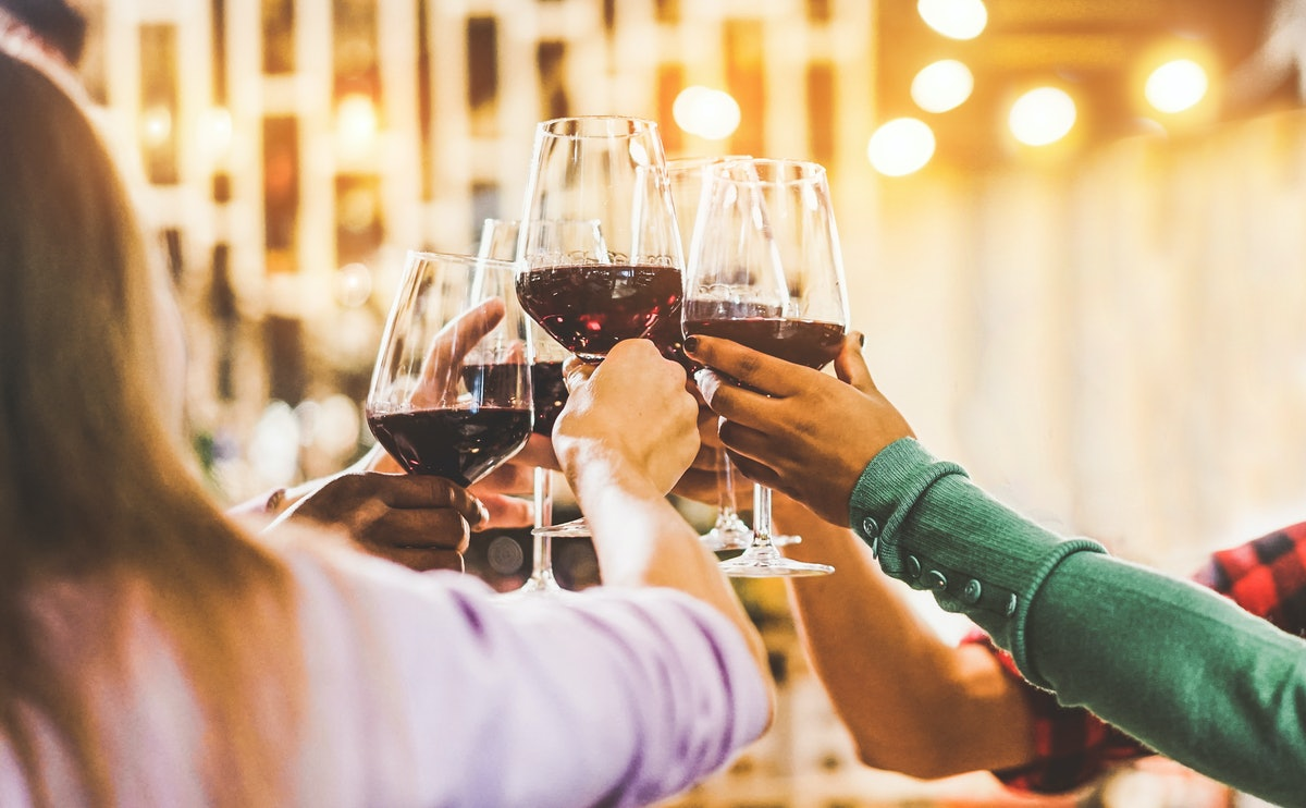 A group of friends cheers with their red wine at a bar.
