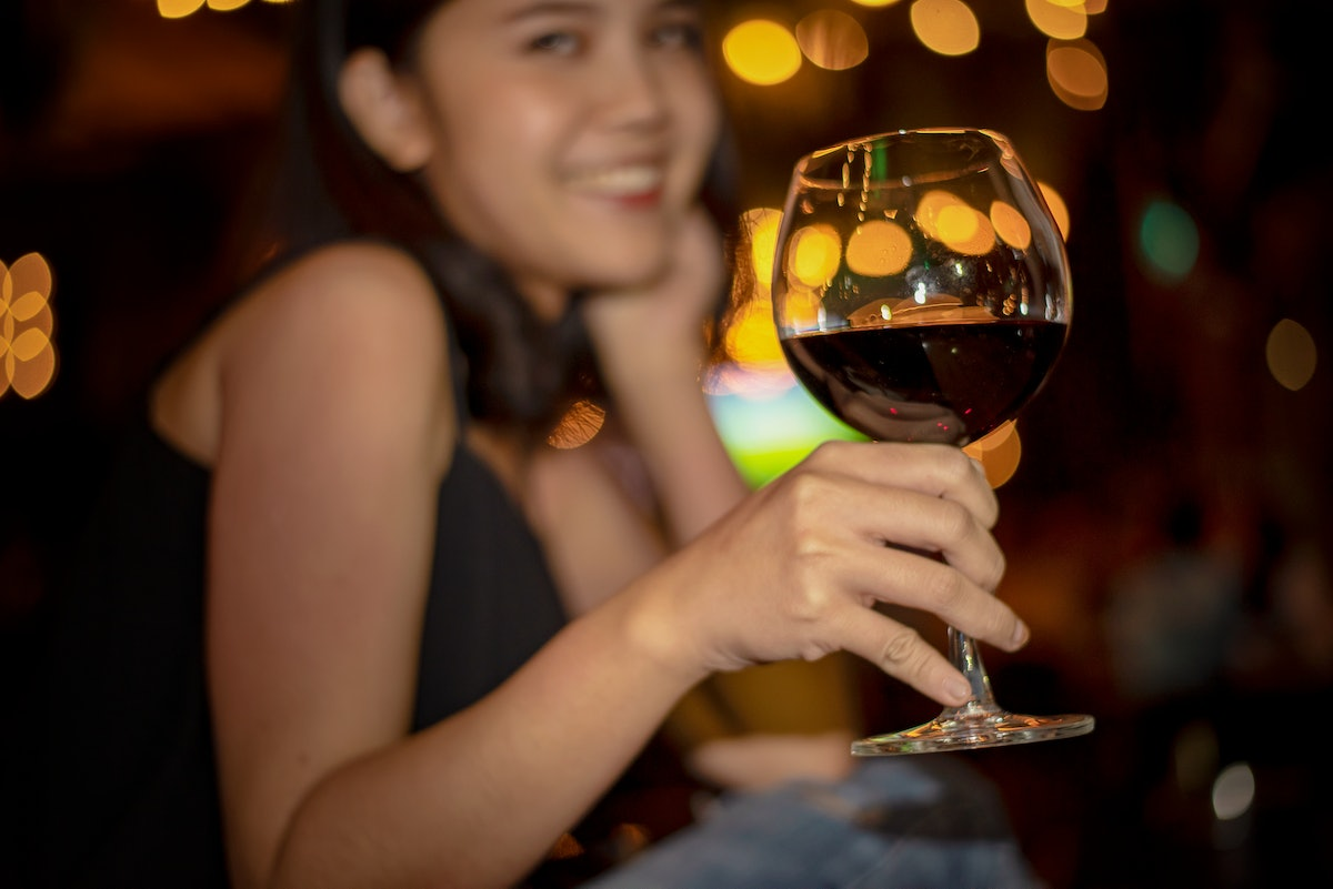 A woman smiles and holds up her wine glass filled with red wine at a restaurant.