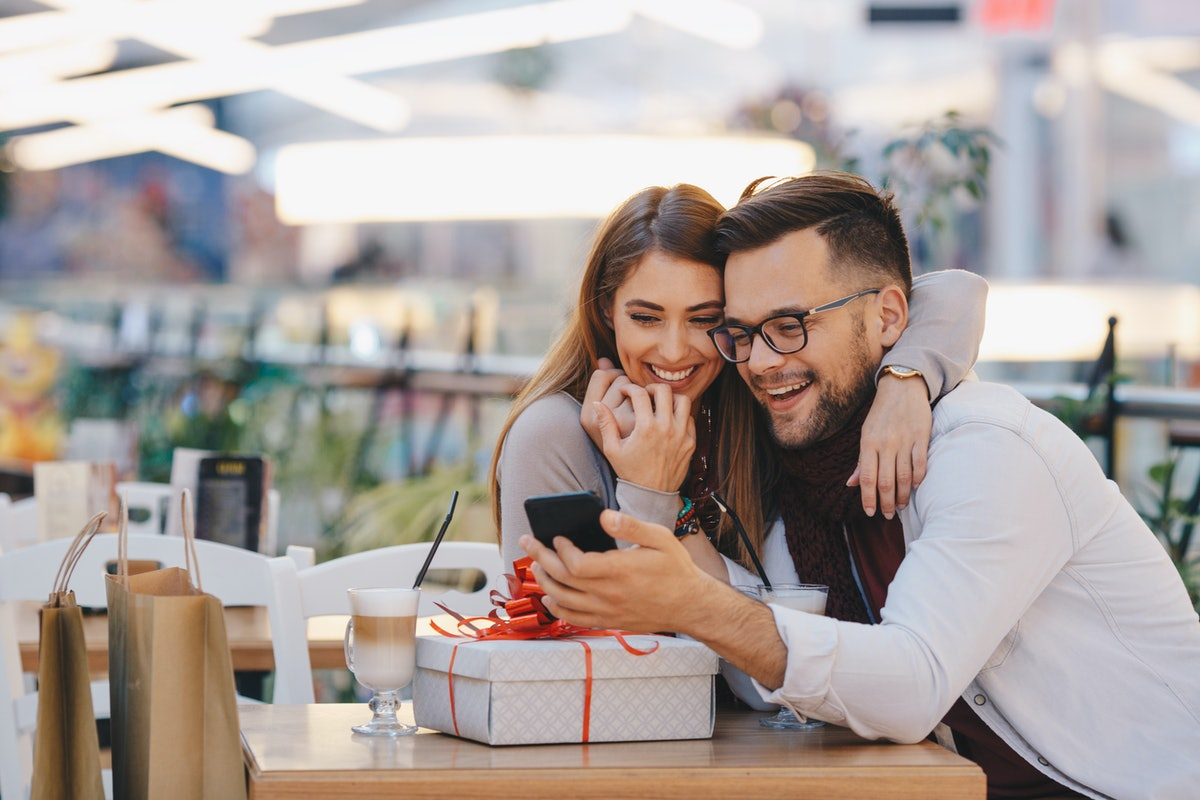 A happy couple sits at a table in a restaurant with a beautifully-wrapped gift and lattes in front of them.