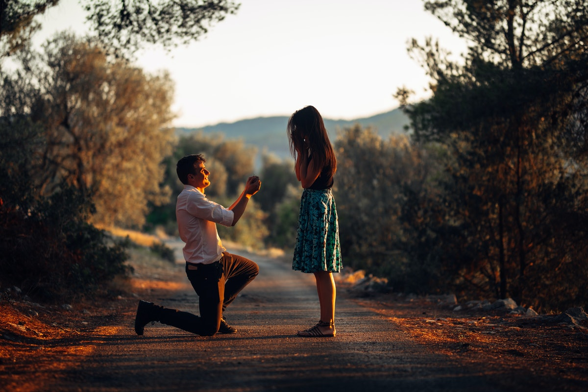 Man in love proposing a surprised,shocked woman to marry him.Proposal, engagement and wedding concept.Betrothal.Being affianced to love of life.Kneeling,getting down on knees.Ring offering.Marriage