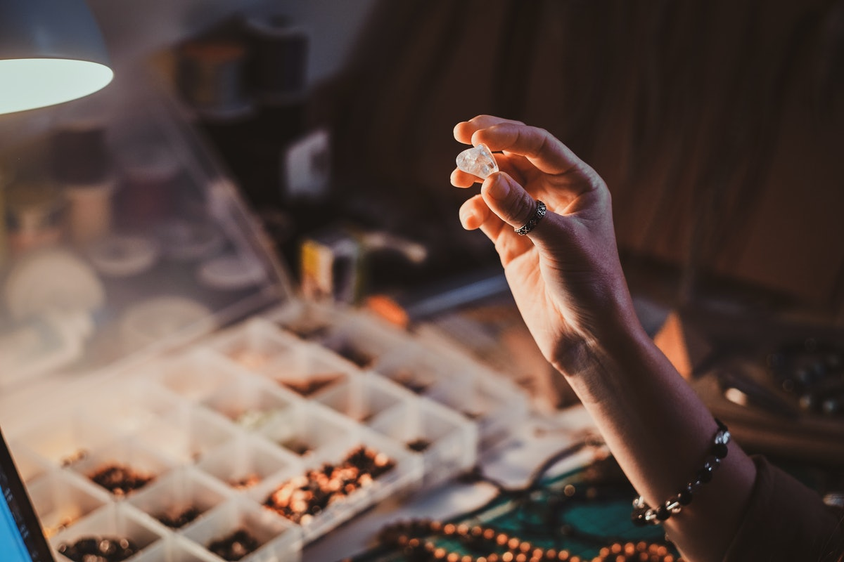 Talented jewellery beads maker is holding crystal clear semi precious stone in hand.