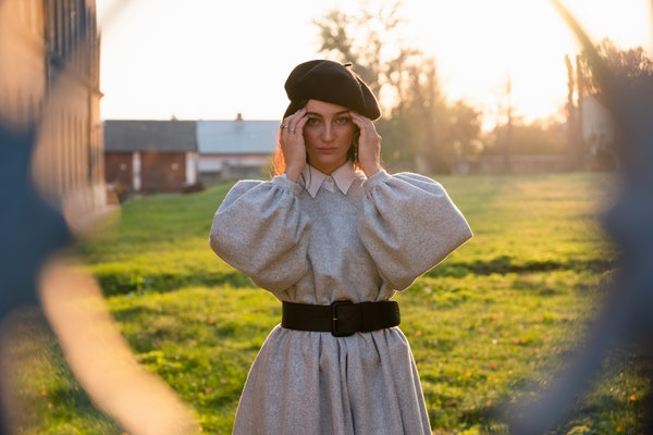 Sad young woman in black beret and grey dress holds her hands near her head, have a headache, stands among the dreen meadow, autumn sunny day