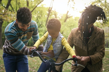 African American parents teaching their little girl to driving bike in park.