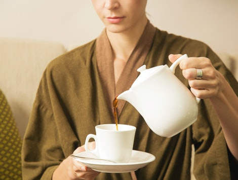 Woman pouring coffee from the kettle into the cup