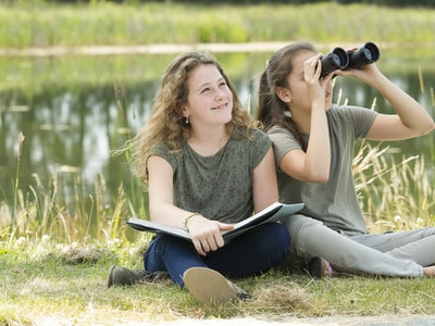 young girls exploring the environment with a binocular