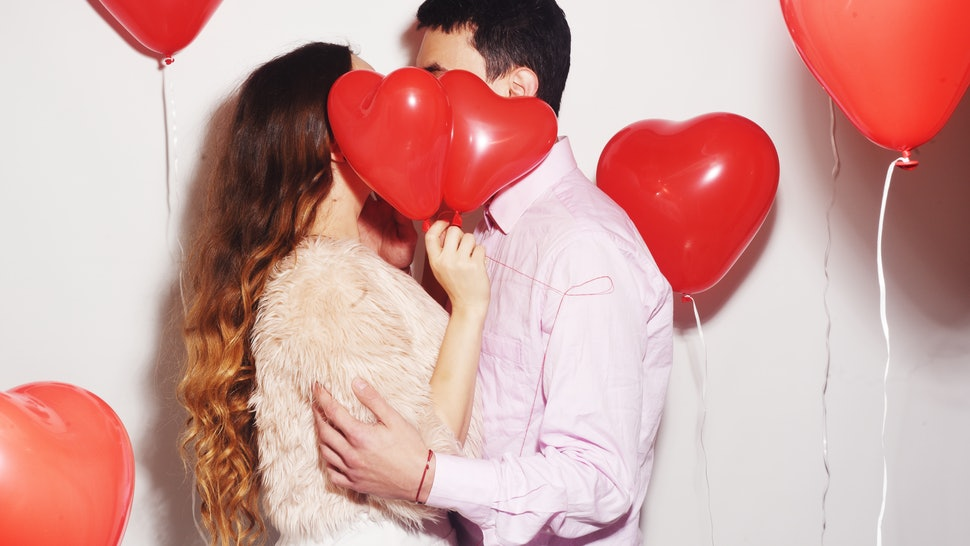 Man with his lovely sweetheart girl dance and have fun at Lover's valentine day. Valentine Couple Party. Background red balloons hearts. Love concept. Crazy.