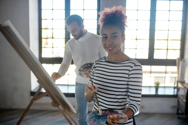 Beautiful young artist. Beautiful young artist standing in spacious room and painting with friend