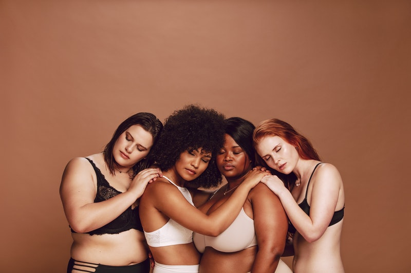Multiracial group women in lingerie hugging each other with their eyes closed. Women of different weight wearing lingerie on brown background.