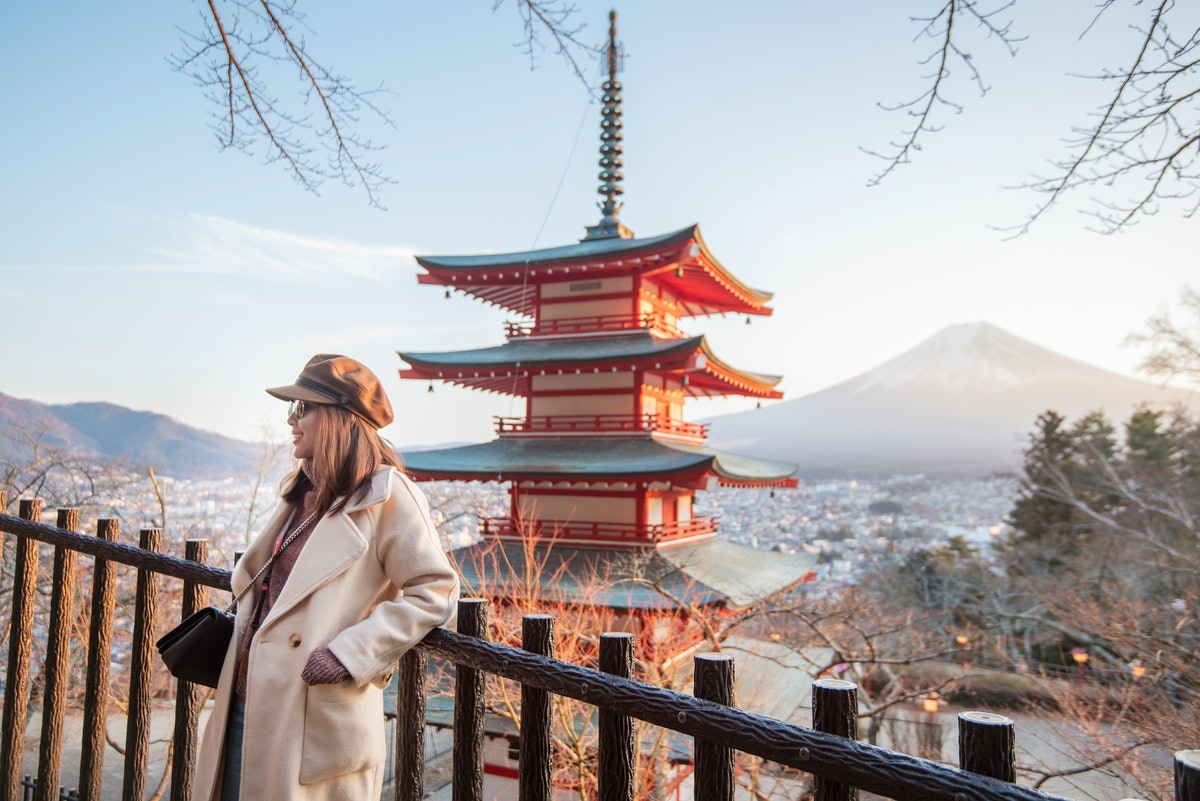 A young woman stands in front of a beautiful view of a temple and Fuji Mountain in Japan.