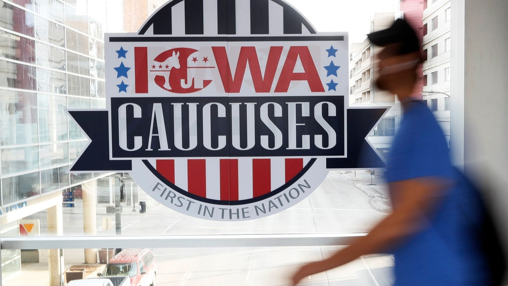 A pedestrian walks past a sign for the Iowa Caucuses on a downtown skywalk, in Des Moines, Iowa