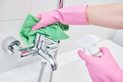 cleaning service. wiping bathroom faucet tap