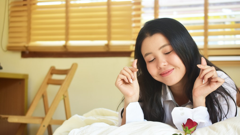 Young beauty women with rose flower is on bedroom