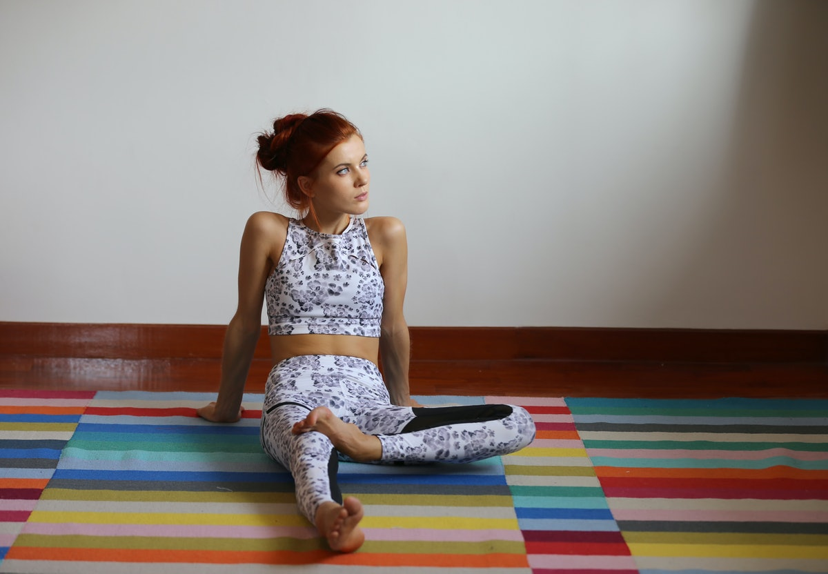 A young woman sits on a colorful yoga mat in a studio in New York City.