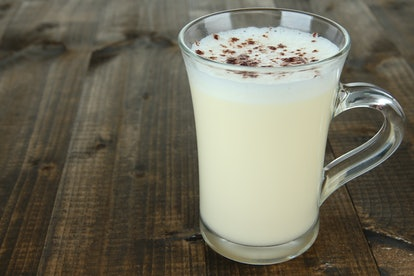 Cup of eggnog on wooden background