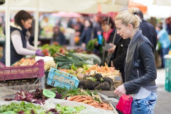 Woman buying fruits and vegetables at local food market. Market stall with variety of organic vegeta...