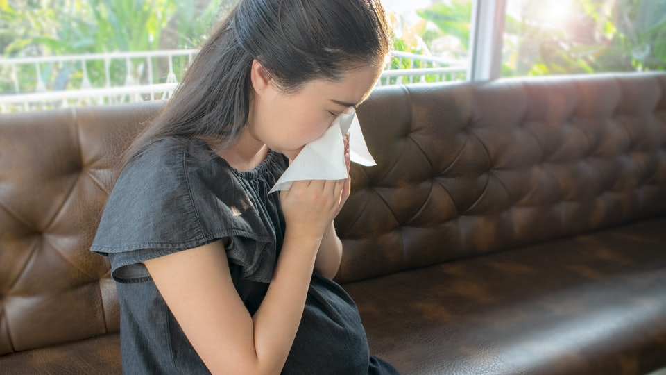 Pretty young pregnant woman feeling sick with a cold and holding a tissue in front of her nose