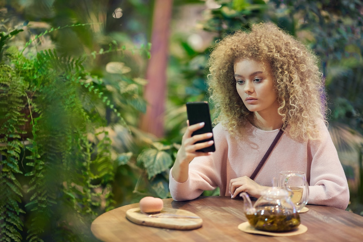 Portrait of young beautiful woman with curly hair using her phone while drinking tea in green cafe
