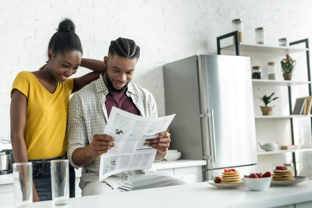 african american couple reading newspaper together at kitchen