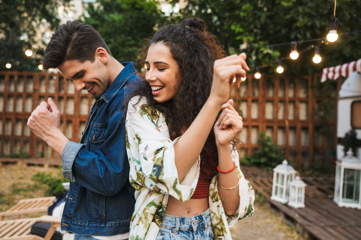 A happy couple dances back to back out in the backyard.