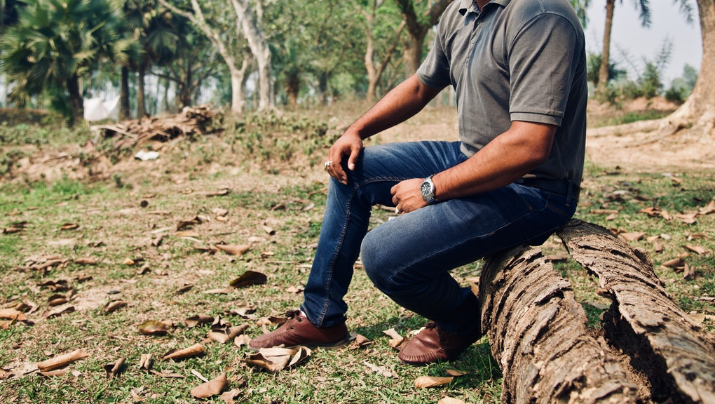 Man wearing jeans sitting on a dead parts of a tree