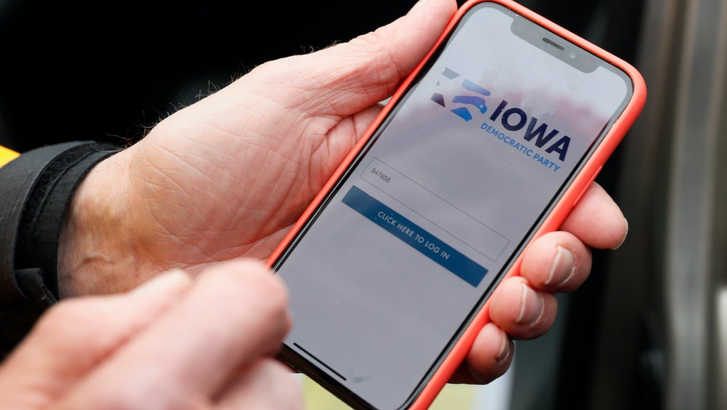 Precinct captain Carl Voss, of Des Moines, Iowa, holds his iPhone that shows the Iowa Democratic Party's caucus reporting app, in Des Moines, Iowa