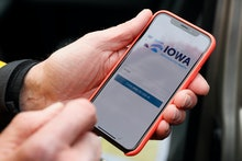 Precinct captain Carl Voss, of Des Moines, Iowa, holds his iPhone that shows the Iowa Democratic Par...