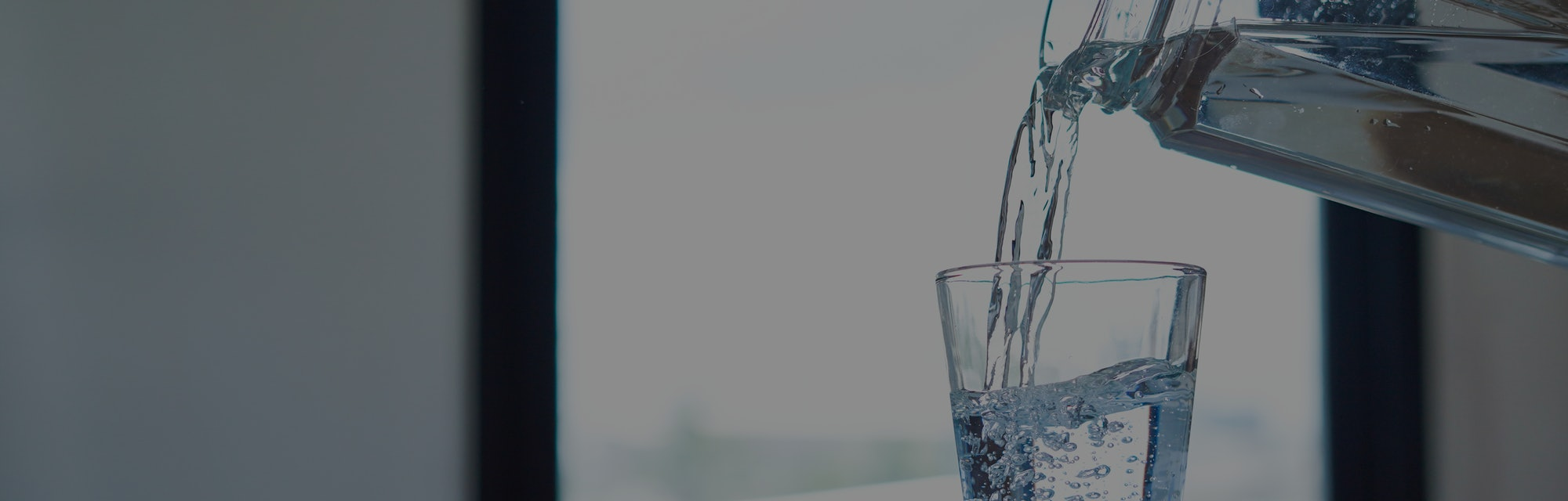 Woman hand holding jar of water and pouring water into a glass.