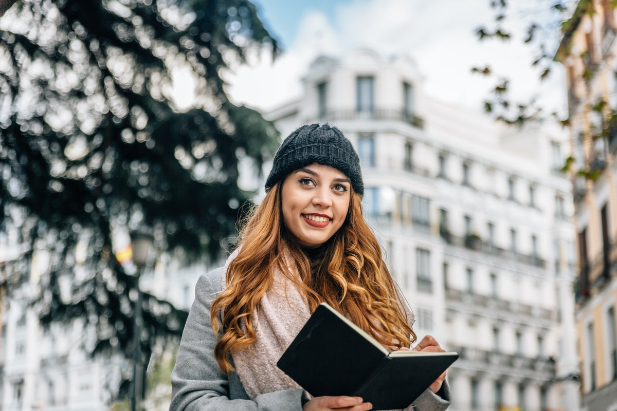 Beautiful smiling blonde girl writes in her black notebook while on the street on a cold day