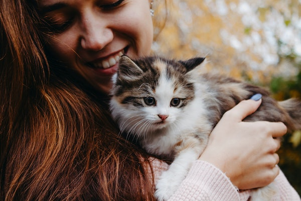 A woman holds a little kitten in her arms and smiles while she looks down.