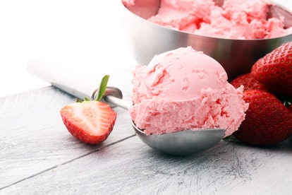 Delicious strawberry ice cream scoop with fresh strawberries on wooden background