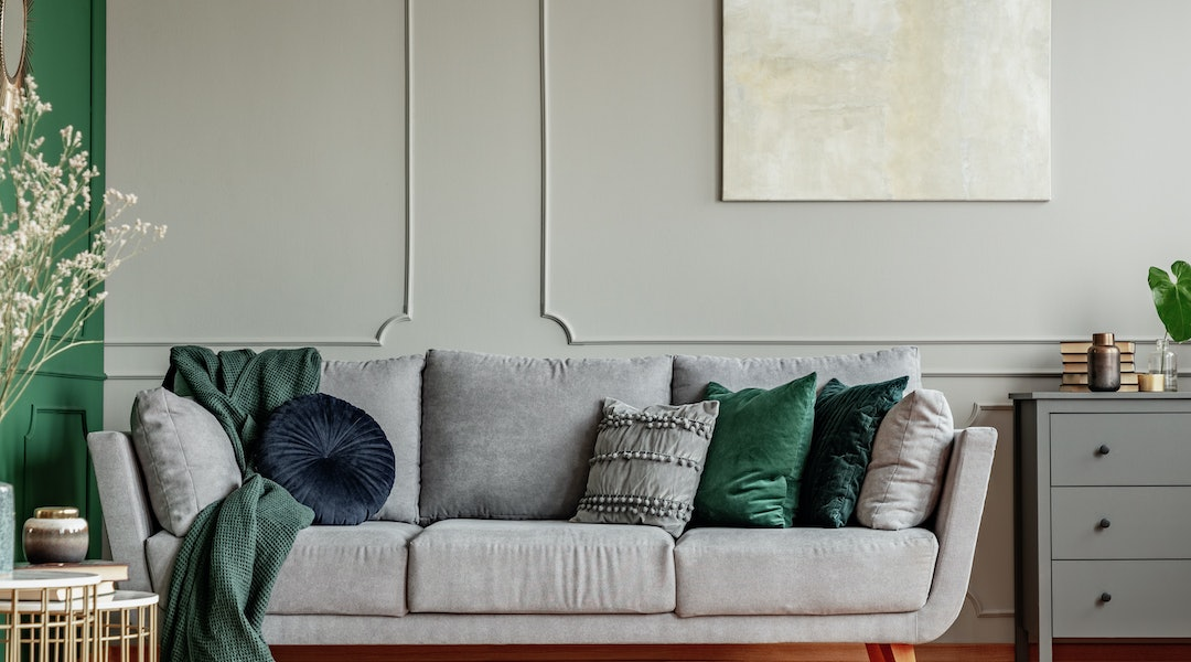 Pillows on long comfortable living room couch in grey scandinavian style interior with wooden floor