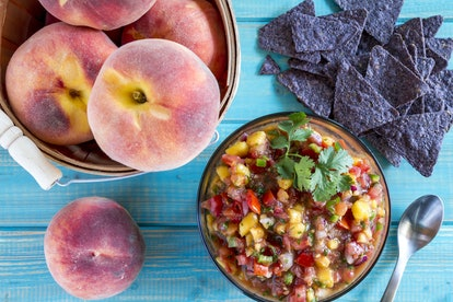 Fresh organic yellow peaches in wooden bushel basket with bowl of homemade peach salsa with spoon and blue corn chips sitting on blue wooden table