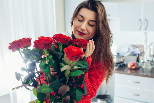 A young woman with red lipstick smells her gorgeous bouquet of roses in her white bedroom.