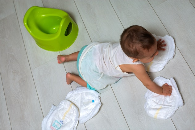 potty training concept. A cute little baby in a room on the bright floor plays with a diaper and an inverted green pot. soft focus, top view