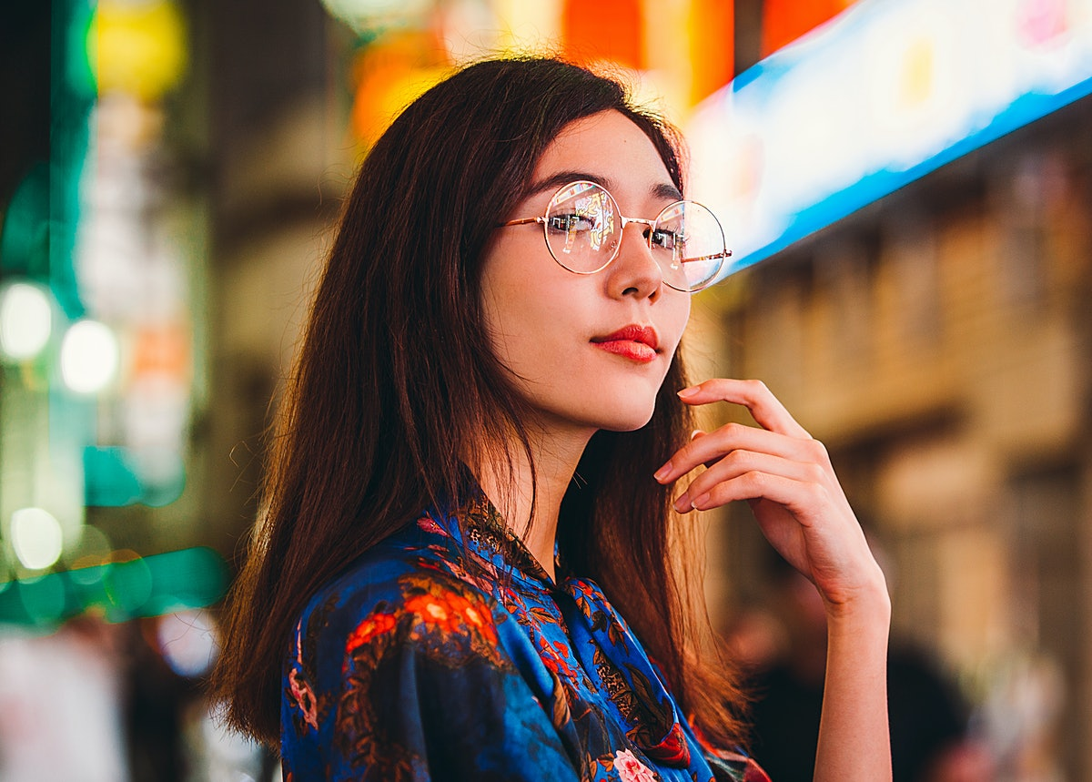 Beautiful mixed race woman posing outdoors, background with blurred neon lights