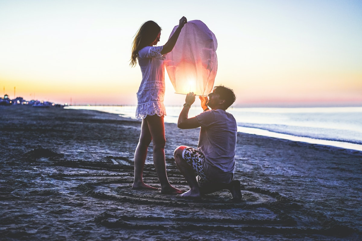 A couple gets a lantern ready on a beach to set off over the water at sunset.