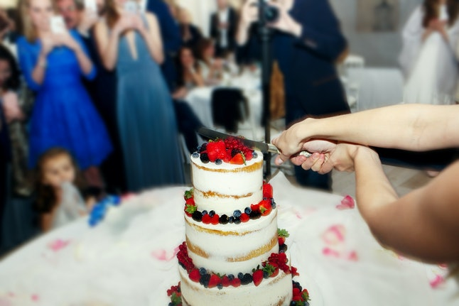 Look from behind on the wedding couple cutting beautiful cake