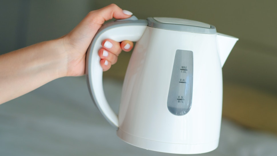 Women hand hold the plastic electric kettle, preparing hot drink, click on the button