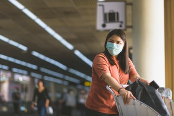 Asian women are traveling to travel within the country. At the airport building She wears a mask to prevent dust and communicable diseases.