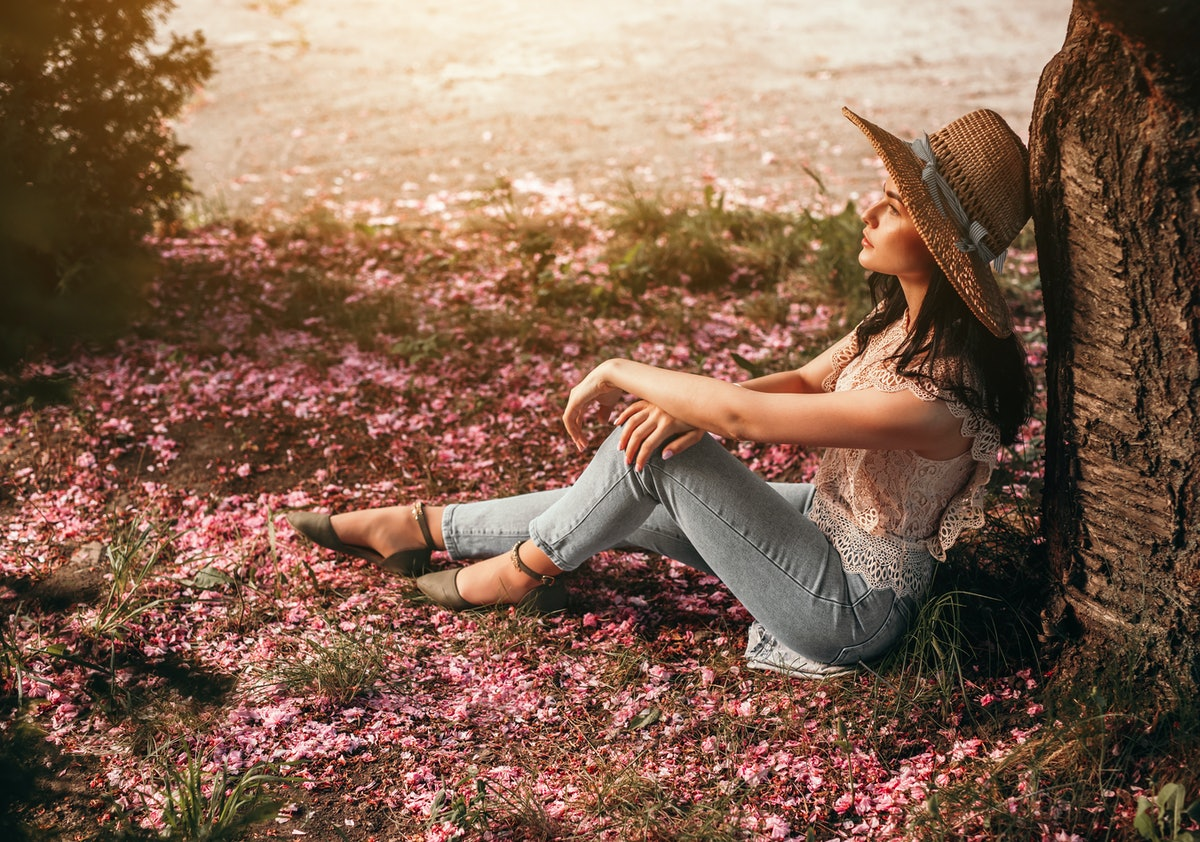 Side view of stylish lady sitting on ground covered with pink flower petals and leaning on tree trunk, while resting in spring park near lake and dreaming