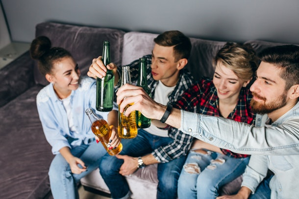 Four friends smile, sit on a couch, and clink their beers.