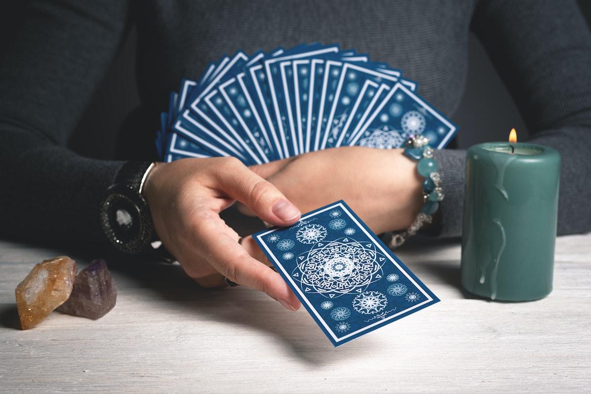 Tarot cards in fortune teller hands concept.