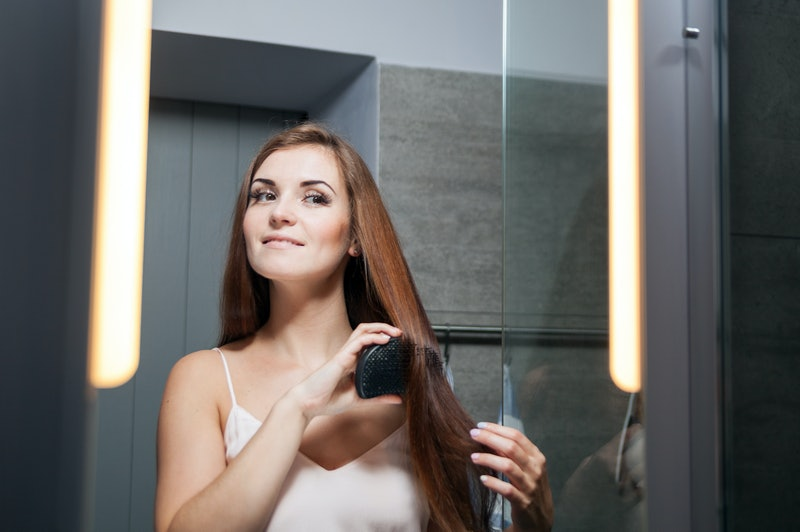 Young woman brushing hair in front of a bathroom mirror