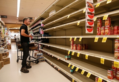A worker looks at empty shelves for canned goods at a supermarket ahead of Hurricane Lane, in Honolu...