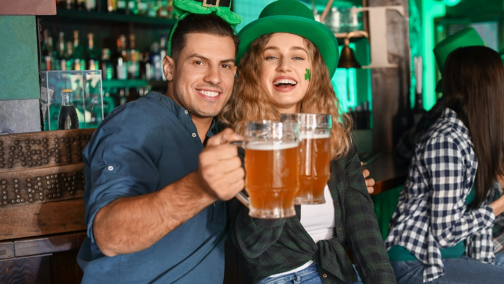 A couple clinks their beers while celebrating St. Patrick's Day.