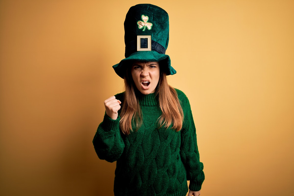 Young beautiful brunette woman wearing green hat on st patricks day celebration angry and mad raisin...