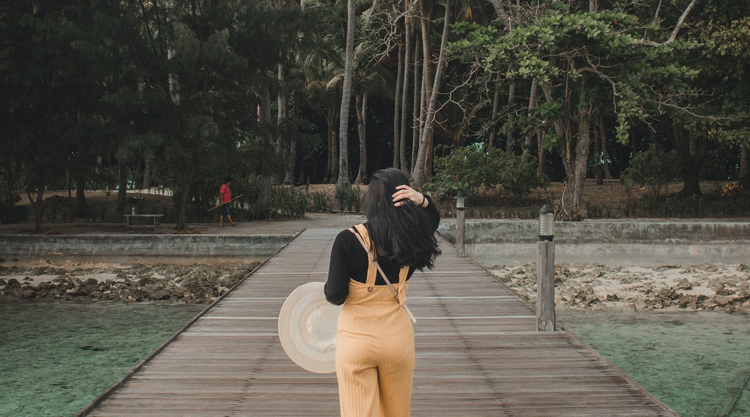 A girl wearing a black and yellow jumpsuit walking away to her solo vacation.
