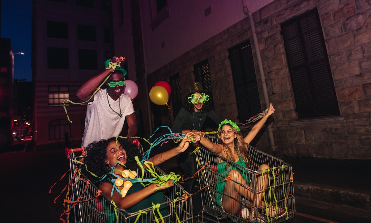 A group of four friends has fun in shopping carts at night with confetti and balloons, celebrating St. Patrick's Day.