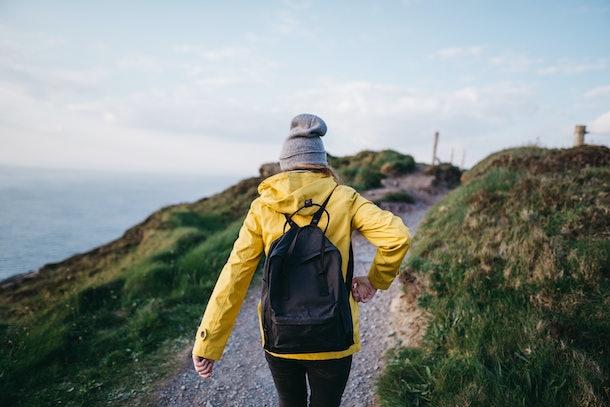 A female backpacker walks along the coast in Ireland.