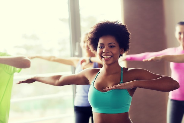 A woman in a turquoise sports bra dances in a studio.